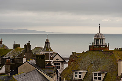 Rooftops of the town of Lyme Regis before a calm, flat sea in the winter. - p1433m2014876 by Wolf Kettler