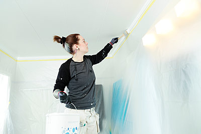 Woman painting ceiling - p312m2191135 by Phia Bergdahl
