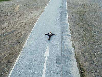 Man arms outstretched lying on country road, aerial view - p586m1088318 by Kniel Synnatzschke