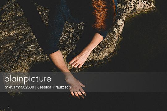 Man liegt auf Stein und hält seine Hand ins Wasser - p1491m1582690 von Jessica Prautzsch