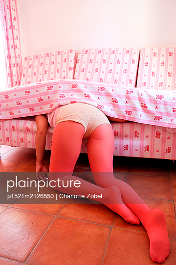 Woman stuck under the cushions of a sofa - p1521m2126550 by Charlotte Zobel