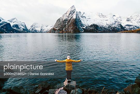 Tourist standing on a rock enjoying the view at Hamnoy, Lofoten, Norway - p300m2166521 by Daniel González