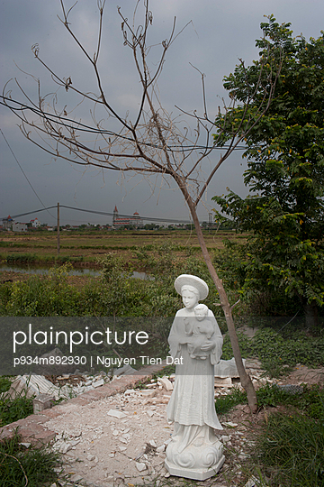 Catholic statue standing on close to rice fields in Nam Dinh, Vietnam, Southeast Asia