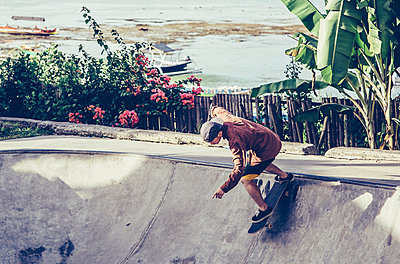 Young man skateboarding on sports ramp at park - p1166m1473879 by Cavan Images