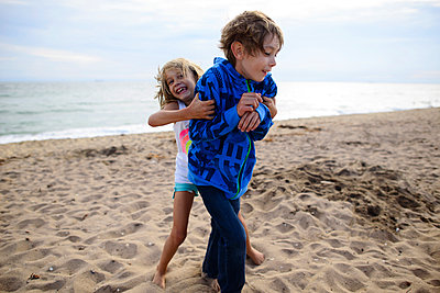 Playful sister tickling brother while standing at Huntington Beach against sky - p1166m1486210 by Cavan Images