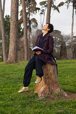 Full length of woman looking up while sitting on tree stump at field - p301m1406360 by Ralf Hiemisch