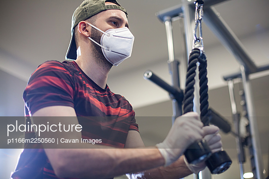 Young caucasian man working out on lat pull-down machine in re-open gym - p1166m2250560 by Cavan Images