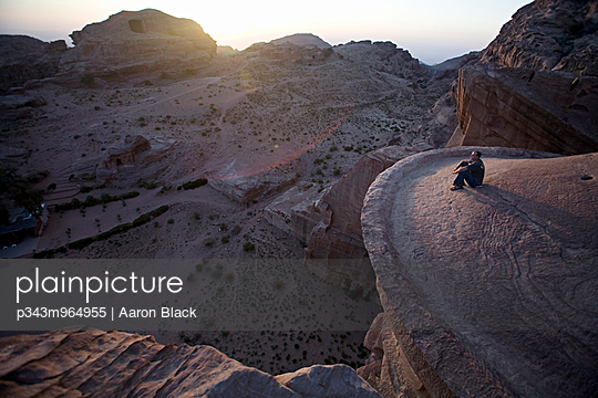 Man sitting on the rim of a massive temple high above the valley floor at sunset. - p343m964955 by Aaron Black