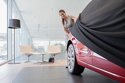 Car saleswoman removing cover from new car in car dealership showroom - p1023m1542408 by Martin Barraud