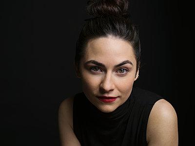 Portrait serious brunette woman against black background - p1192m1403541 by Hero Images