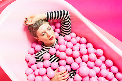 Woman lying in a bathtub with pink plastic balls  - p1332m2055049 by Tamboly