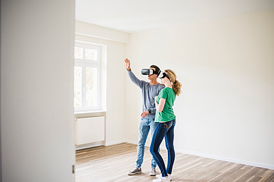 Young couple in empty apartment wearing VR glasses - p300m1460718 by Uwe Umstätter