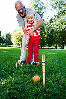 Girl and senior man playing croquet in the park Sweden. - p31221395f by Plattform