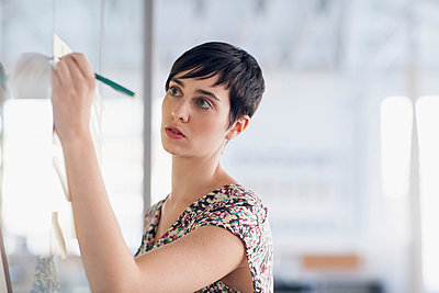 Stylish young businesswoman writing on whiteboard. - p328m784083f by Hero Images