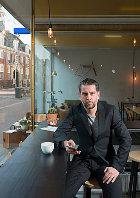 Portrait of cool businessman sitting at cafe window seat with smartphone - p429m1135396f by Mischa Keijser