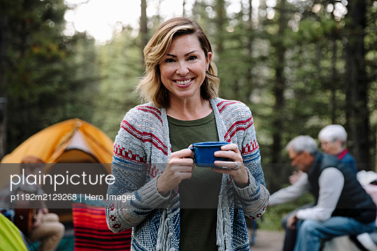 Portrait happy woman drinking coffee at campsite - p1192m2129268 by Hero Images