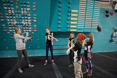 Female instructor and girl rock climber students stretching arms, preparing at climbing wall in climbing gym - p1192m1560057 by Hero Images
