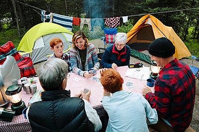 Multi-generation family playing cards at campsite picnic table - p1192m2129281 by Hero Images