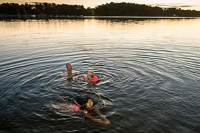 Vater und Kinder baden im See - p1418m1590281 von Jan Håkan Dahlström