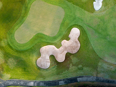 Indonesia, Bali, Aerial view of golf course with bunker and green - p300m2023860 by Konstantin Trubavin