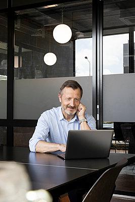 Smiling businessman working on laptop at desk in office - p300m2287346 by Florian Küttler