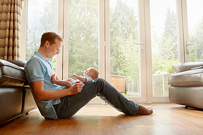 Mature man sitting on floor with baby son on his lap - p429m1408043 by Emma Kim