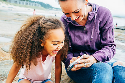 Mother and daughter using cell phone on beach - p555m1311466 by Inti St Clair photography