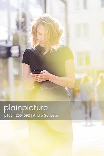 Junge benutzt ein Smartphone in der Stadt - p105m2064092 von André Schuster