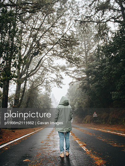 Rear view of young woman in jacket standing on asphalt road in forest - p1166m2111662 by Cavan Images