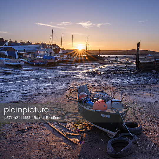 The sun sets behind the boats at Camperdown, Exmouth, Devon, England, United Kingdom - p871m2111483 by Baxter Bradford