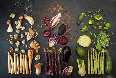 Flat lay of various fresh vegetables on black table - p1166m2034438 by Cavan Social