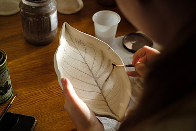 Woman potter paints a ceramic leaf - p1363m2054119 by Valery Skurydin