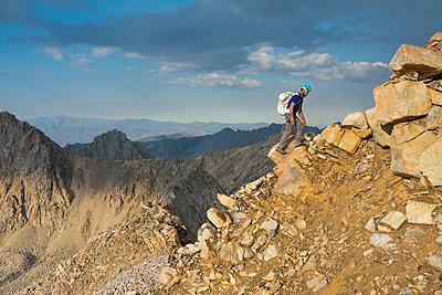 Man climbing on mountain - p343m1446742 by Kennan Harvey