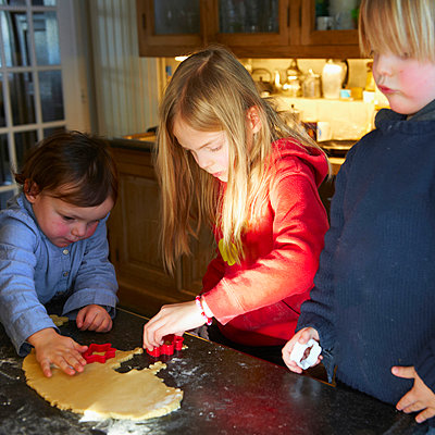 Brother and sisters making biscuits in kitchen - p429m929525f by Ghislain & Marie David de Lossy
