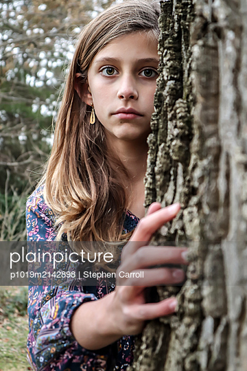 Girl behind a tree - p1019m2142898 by Stephen Carroll