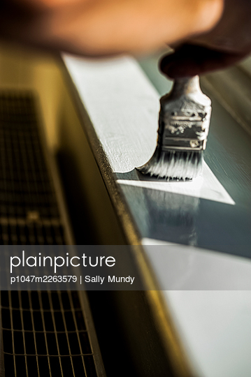 Hand holding paintbrush applying white gloss paint to windowsill above radiator - p1047m2263579 by Sally Mundy