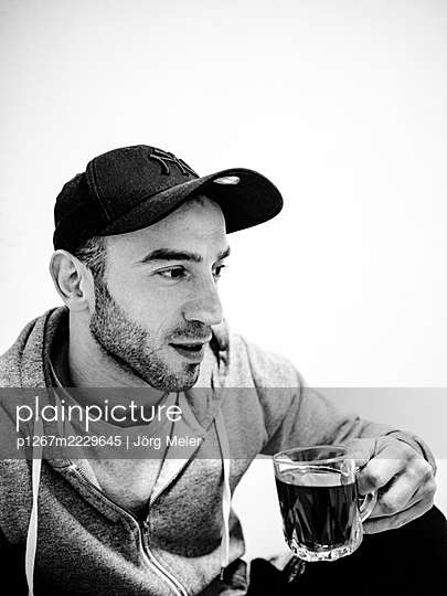 Man with baseball cap has a cup of tea - p1267m2229645 by Jörg Meier