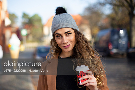 Young woman with coffee to go - p975m2222098 by Hayden Verry