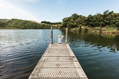 Toddler boy sitting on a wooden dock at a lake - p1166m2130880 by Cavan Images