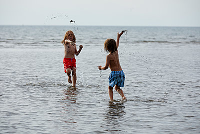 Two children playing in shallow water - p1511m2223063 by artwall
