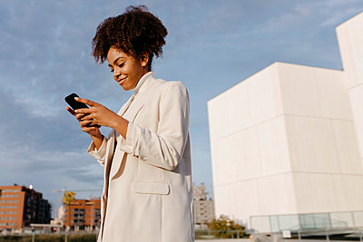 Smiling young woman with afro hair using smart phone while standing against sky in city - p300m2257325 by Tania Cervián