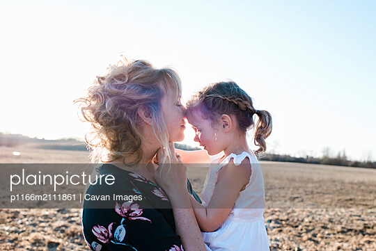 mother holding daughter cuddling and smiling at sunset in summer - p1166m2111861 by Cavan Images