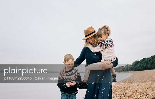 mom and her kids enjoying a walk together on the beach in England - p1166m2268845 by Cavan Images