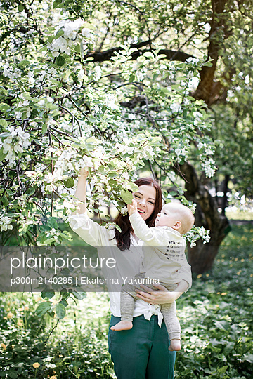 Mother with her baby boy at a tree in park - p300m2140295 by Ekaterina Yakunina
