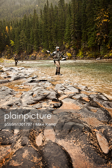 Caucasian men fishing in river - p555m1301797 by Mike Kemp