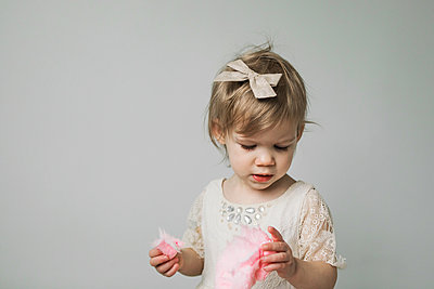 Toddler eating pink cotton candy - p1166m2153426 by Cavan Images