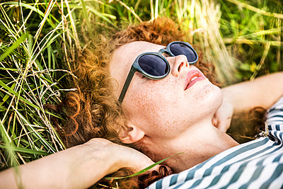 Young woman wearing sunglasses relaxing on a meadow - p300m2029071 by Jo Kirchherr