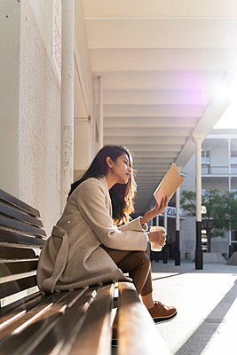 Young woman with takeaway coffee reading book on a bench - p300m2166203 by VITTA GALLERY