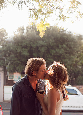 Couple kissing on street during sunny day - p300m2224980 by LOUIS CHRISTIAN