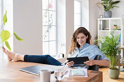 Smiling female entrepreneur looking at digital tablet while sitting with feet up at desk - p300m2277535 by Steve Brookland
